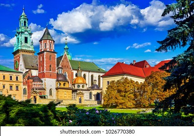Wawel castle in Krakow, Poland. Towers of vintage fortress and Catholic temple. Picturesque territory in autumn day with yellow and green trees. Blue sky with clouds.
