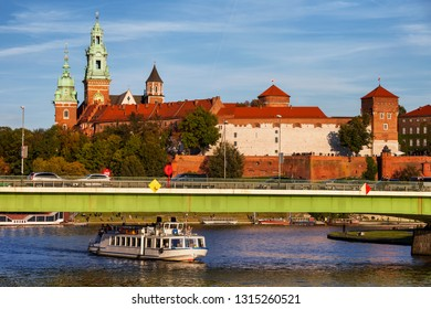 Wawel Royal Castle in city of Krakow in Poland, passenger tour boat and bridge on the Vistula River