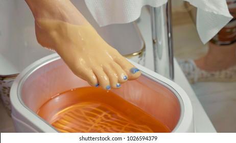 Wax bath for feet at beauty spa salon, close-up. Paraffin wax treatments for feet.