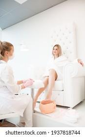 Wax bath for feet at beauty spa salon. Paraffin wax treatments for feet.
