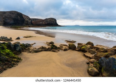 The Wax Beach (Playa de la Cera) tourist attraction in Lanzarote, Canary Islands, on a beautiful summer morning. Empty beach with volcanic rocks, golden sand and clear turquoise water.