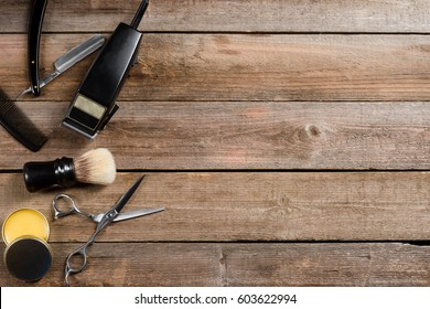 Wax, brush, an electric clipper, scissors, a comb and vintage straight razors on the wooden background. Place to insert your text. Barber shop.
