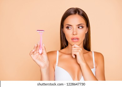 Wax or shave? Close up portrait of thinking lady look aside on safety razor she isolated on pastel beige background with her worried face