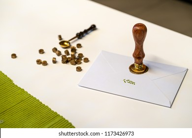 wax seal stamp and utils on envelope on white table