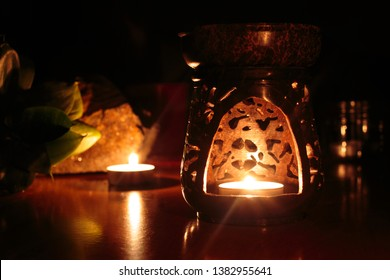 Wax warmer, wax melt, warmer candle with candle light inside. Picture was took with natural light from the fire. In the background are stone and plant.