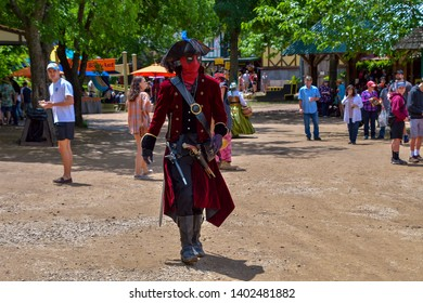 Waxahachie, Texas / USA - 12 May 2019 Scarborough Renaissance Festival Man dressed as Deadpool and Pirate walking down the muddy street, watched by festival attendees.