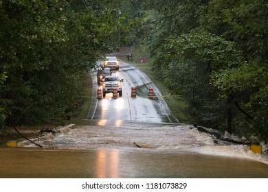 Waxhaw, North Carolina - September 16, 2018: Motorists are blocked from crossing a road flooded by rainwater from Hurricane Florence