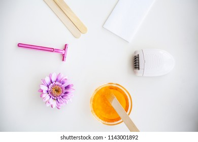 Waxing. Set for Epilation Of different Means For Epilation on a White Background. Removal of Unwanted Hair. Modern Epilator, Wax Strips, Razor. Minimalist, Top View.