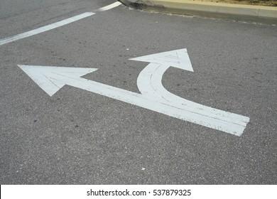 A way arrow symbol on a black asphalt road surface.