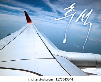 The way to hometown. Calligraphy Translated : Chuseok(Korean Thanksgiving Day) Background : Wing of the Airplane and Blue Sky and clouds.