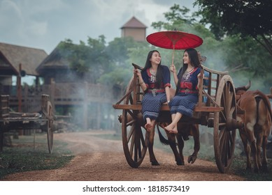 The way of life of Thai women from ancient times in traditional Thai costumes, sitting on a bullock cart or riding a cart. The backdrop is a beautiful ancient wooden house in Thailand.