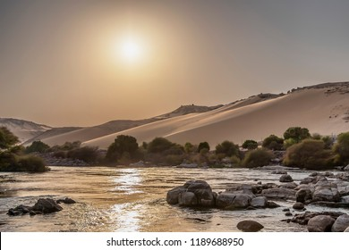 In the way to the Nubian village at sunset, sailing the Nile river through the dunes of the desert Aswan, Egypt