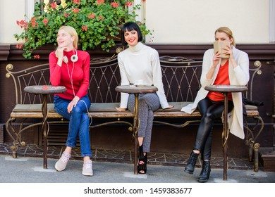 Way to relax and recharge. Female leisure. Hobby and leisure. Different interests. Weekend relax and leisure. Group pretty women terrace entertain themselves with reading and listening. Coffee cafe.