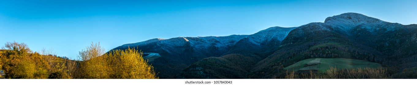 Way of St James, Panoramic snow-capped mountains with blue sky and green fields. Wide. Galicia, spain.