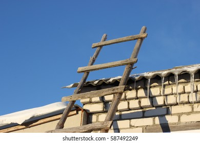the way up the stairs to the roof. Snowdrift on an old roof of asbestos cement shingle. Wall of a house made of sand-lime bricks. Wooden staircase. Cloudless blue sky. Stairs, winter, sunny day.