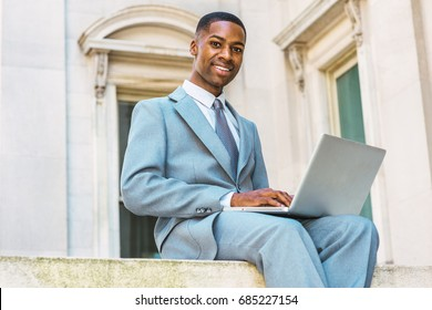 Way to success. African American Businessman working in New York. Male college student dressing formally in suit, tie, siting outside vintage office building on campus, working on laptop computer.
