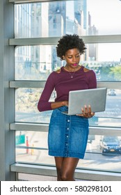 Way to success. African American college student with short afro hairstyle stands against glass wall on campus in New York, works on laptop computer. Street, cars on background.