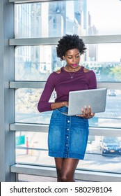 Way to success. African American college student with short afro hairstyle stands against glass wall on campus in New York, works on laptop computer. Street, cars on background. Color filtered effect