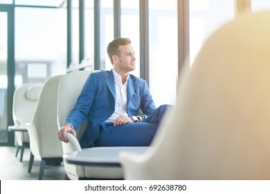 Way to success. Cheerful confident young handsome businessman sitting at the table in the restaurant and looking in the window while resting after work