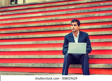 Way to Success. East Indian American College Student studies in New York. Wearing black suit, white shirt, young man sits on stairs on campus, works on laptop computer, thinks. Filtered effect.