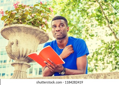 Way to Success. Young African American College Student studying in New York, wearing blue short sleeve T shirt, standing, back bending forward on top of wall on campus, hand holding red book, thinking