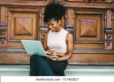 Way to Success. Young African American woman with afro hairstyle wearing sleeveless light color top, black skit, sitting by vintage office door in New York, working on laptop computer, smiling.