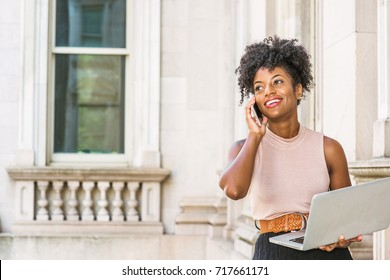 Way to Success. Young African American Businesswoman with afro hairstyle, sitting in vintage style office building in New York, working on laptop computer, making phone call, looking up, smiling,