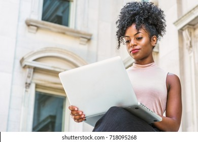 Way to Success. Young African American woman with afro hairstyle wearing sleeveless light color top, sitting by vintage office building in New York, looking down, reading, working on laptop computer.
