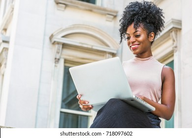 Way to Success. Young African American woman with afro hairstyle wearing sleeveless light color top, sitting by vintage office building in New York, looking down, working on laptop computer, smiling.