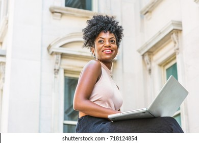 Way to Success. Young African American woman with afro hairstyle wearing sleeveless light color top, sitting by vintage office building in New York, working on laptop computer, looking up, smiling.