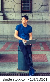 Way to Success. Young Asian American Man studying, working in New York, wearing blue T shirt, black pants, sneakers, sitting on pillar on street on campus, working on laptop computer, thinking.