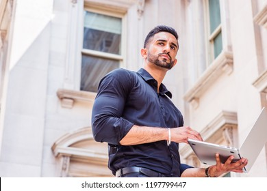 Way to Success. Young East Indian American Businessman with beard working in New York, wearing black shirt, holding laptop computer, standing outside old style office building, looking up, thinking.