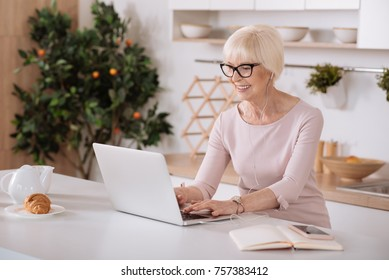 Way of timespending. Cheerful senior woman listening to music and using her laptop while sitting in the kitchen