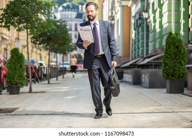 Way to work. Cheerful adult man walking along the street while reading a newspaper