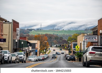 Waynesboro, USA - October 27, 2020: Downtown and mist fog clouds in small town city with Main street in rural Virginia and cars parked by stores shops building on cloudy day