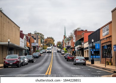 Waynesboro, USA - October 27, 2020: Downtown in small town city with Main street in rural Virginia and cars parked by stores shops building on cloudy day