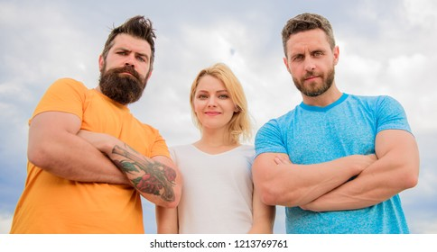 Ways to build cohesive team. Strength in unity. Woman and men look confident sky background. Threesome stand confidently with folded arms. Behaviors of cohesive team. Threesome look down at you.
