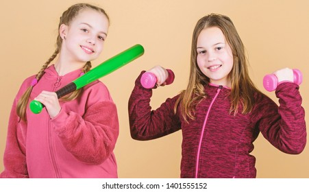 Ways to help kids find sport they enjoy. Girls cute kids with sport equipment dumbbells and baseball bat. We love sport. Child might excel in completely different sport. Friends ready for training.