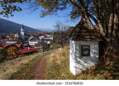 Wayside shrine on calvary chapel path, autumn, Bad Hindelang and parish church of St. John the Baptist behind, Allgäu, Bavaria, Germany