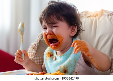 Wayward little toddler child or infant baby crying that don't want eating food on baby chair Cute infant children get hungry and want new food Children get dirty Kid get tantrum Baby is stubborn baby
