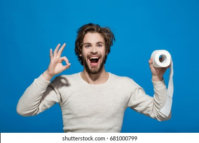 WC and restroom. Hygiene and sanitary. Man with happy face hold toilet paper. Sterility and purity. Guy in underwear in morning with ok gesture.