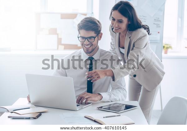 すでに素晴らしい結果が出ています!若い美しい女性は、ラップトップを笑顔で指さし、会社に立って同僚と何かを話し合う