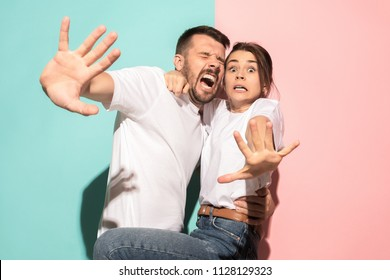 We are in awe. Fright. Portrait of the scared man and woman. Couple standing on trendy pink and blue studio background. Human emotions, facial expression concept. Front view