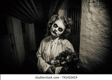 We bleed together.Scarry horror movie scene with creepy clown girl holding a bleeding doll in a dark room