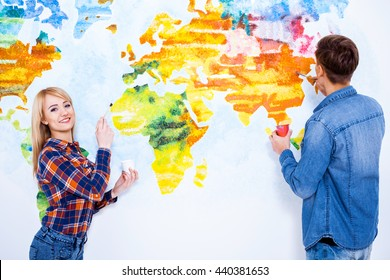 We can paint whatever you want. Beautiful young couple painting map of the world on the wall.