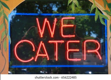 We Cater Red and Blue Neon Sign in Restaurant Window