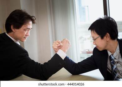 We are in a competitive business. We are in a competitive business. Two businessmen arm wrestling. Modern office background