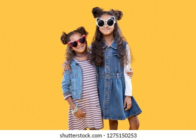 We are cool. Joyful happy sisters hugging each other while standing against yellow background