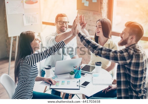 We did it! Four cheerful young people giving highfive to each other and smiling at the nice sunny day after they have done start up project together