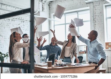 We did it! Group of young confident business people throwing paper in air while working behind the glass wall in the board room